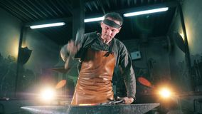 One blacksmith uses a hammer while working with knife at a forge. 4K stock footage