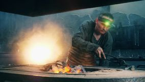 One blacksmith uses tongs to heat a metal knife in fire. 4K stock video footage