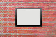 One blank billboard attached to a buildings exterior brick wall Stock Photography
