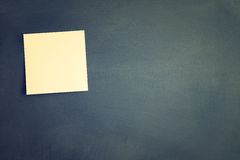One blank sticky note attached to blackboard. Royalty Free Stock Photo