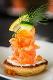 One Blini appetizer with smoked salmon and sour cream, garnished Stock Photo