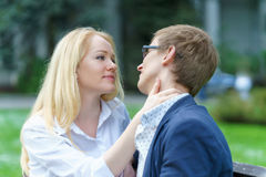 One blond european woman holding neck of her lover and waiting his kissing in some park at warm summer day royalty free stock photo