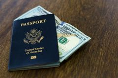Blue American passport with some US dollars on top of a wooden desk. One blue American passport with some one hundred dollar bills on top of a wooden desk top Stock Photography