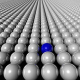 One blue ball in amongst many white balls Stock Photography