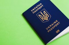 One blue biometric ukrainian foreign passport with coat of arms for visa-free travel on green background with copy space. Visa-free travel concept stock photos