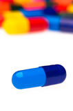 One blue capsule in front of many colorful Royalty Free Stock Images