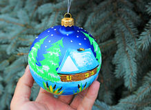 One blue christmas ball handing on a tree. Stock Photo