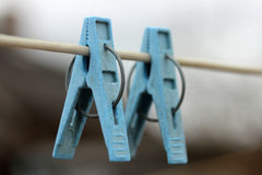One blue clothespins close-up hanging on a rope for drying clothes Royalty Free Stock Image