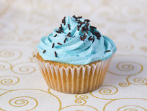 One blue cupcake on a tablecloth Stock Photo