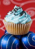 One blue cupcake and two christmas balls Stock Photo