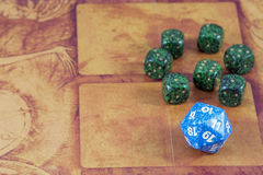 One blue dice with seven green dices on the orange background Stock Images