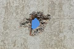 Blue hole on old gray concrete wall of a fence. One blue hole on old gray concrete wall of a fence stock images