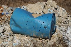 Blue old rumpled plastic barrel lies on a pile of garbage on the street stock photo