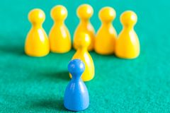 One blue pawn in front of several yellow pawns stock photos