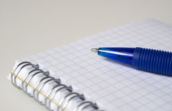Blue pen and notebook. One blue pen and notebook with white sheets close Royalty Free Stock Images