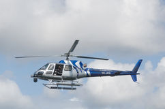 One blue and silver helicopter in the sky Stock Image