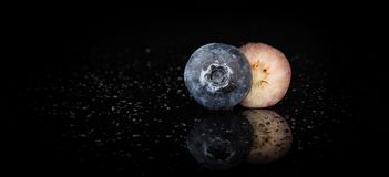 One Blueberry cut in half on a reflective surface, water droplets, black background close up. One Stunning Blueberry cut in half on a reflective surface, water royalty free stock photo