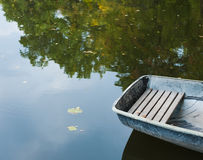 One boat on a summer water of pond. One boat on summer water of pond Stock Photo