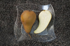 One Bosc pear and a half. Royalty Free Stock Images