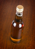 ONE BOTTLE WITH WOODEN BACKGROUND. One small glassy bottle with wooden background stock image