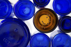 One of these bottles is not like the others. A unique brown glass bottle amongst several different size cobalt blue glass bottles stock images