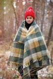 One boy in plaid walks in the snow in the autumn forest. alone i Royalty Free Stock Image