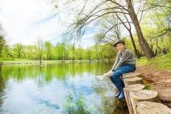 One boy sitting near pond holding white paper boat Stock Photos