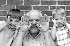 Grandpa and grandsons playing with hand moustaches Stock Images