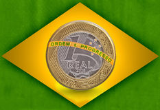 One Brazilian Real flag with a one real coin inside Stock Photos