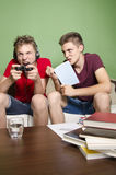 One brother study, while other plays video games Royalty Free Stock Photography