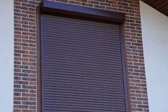 Brown closed rollt on the window in the wall of a brick wall royalty free stock photography