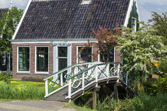 One brown house near the small white bridge with green trees around it. In the summer in the Netherlands Stock Photos