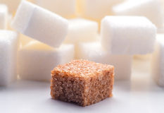 One brown sugar lump in front of lot of white sugar cubes Royalty Free Stock Photos