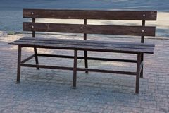 One brown wooden bench stands on a gray sidewalk outside stock photos