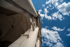 One building overhead and the sky and clouds. Extreme Perspective looking straight up from the base of a historic building. Featured as well is the sky and Stock Photo