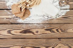 One bundle of wheat and poppy and flour poured out of glass and slices of bread on old wooden planks royalty free stock photos
