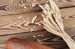 One bundle of wheat and poppy and lot of scattered grain and single whole bread on old wooden planks stock photography