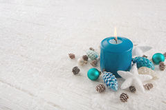 One burning advent candle in turquoise, brown and white colors f Royalty Free Stock Image