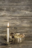 One burning advent candle on wooden christmas background. One white burning advent candle on wooden christmas background Royalty Free Stock Photo