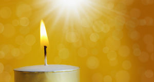 One burning candle with bright white light Royalty Free Stock Image