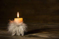 One burning candle with feathers on old wooden background. Stock Photo