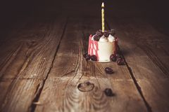 One burning candle in a festive cake cake with cherry fruits on a rustic wooden table on a dark background. close up copy space. Vintage pattern on dessert royalty free stock photo