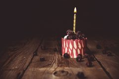 One burning candle in a festive cake cake with cherry fruits on a rustic wooden table on a dark background. close up copy space. Vintage pattern on dessert royalty free stock images