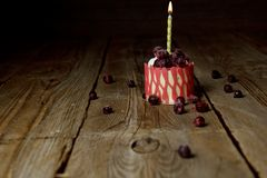 One burning candle in a festive cake cake with cherry fruits on a rustic wooden table on a dark background. close up copy space. Vintage pattern on dessert stock photos