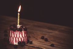 One burning candle in a festive cake cake with cherry fruits on a rustic wooden table on a dark background. close up copy space. Vintage pattern on dessert stock images