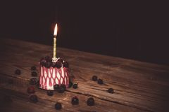One burning candle in a festive cake cake with cherry fruits on a rustic wooden table on a dark background. close up copy space. Vintage pattern on dessert stock image