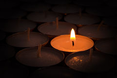 One burning candle lights others Stock Photo