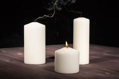 One burning candle and two extinguished. One burning candle extinguished and two on a wooden table stock image