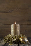 One burning golden advent candle on wooden rustic background. Royalty Free Stock Images