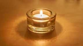One Burning Tea Light Candle on Gold Stock Images